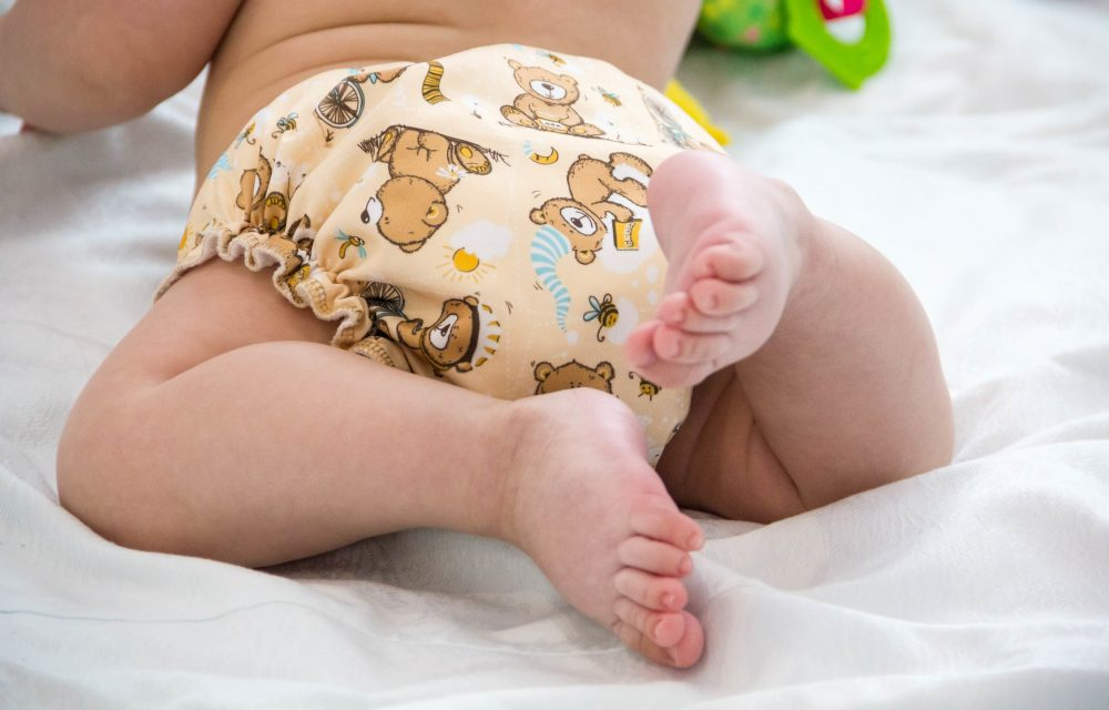 baby in modern eco stacks of cloth diapers and replacement bushings selective focus close-up bright background, little cute foot kid, the concept of health. hygiene of the child. reusable diapers