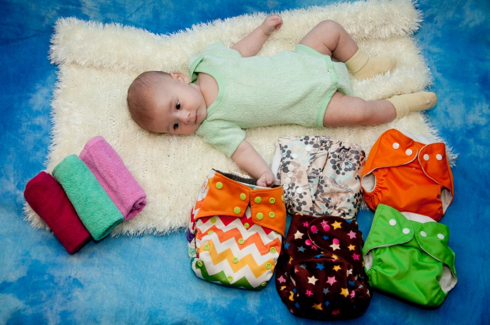 Infant laying on white, blue background near colorful cloth diapers