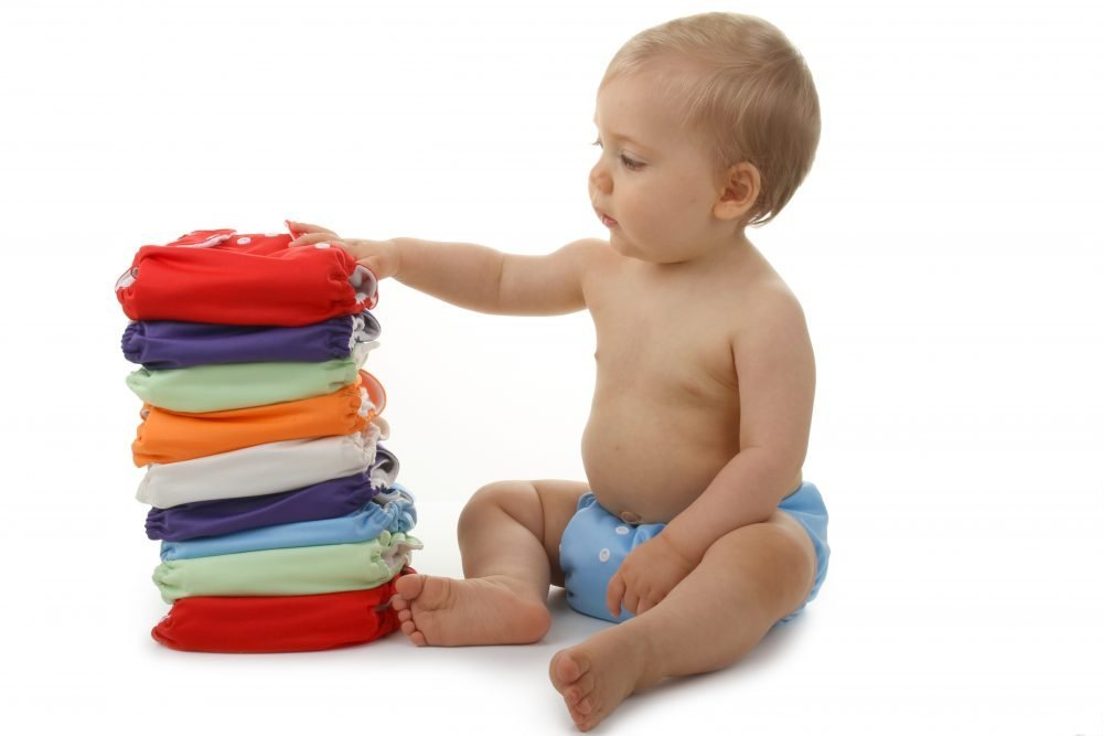 baby sitting beside a stack of cloth diapers