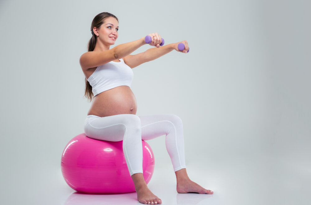 Portrait of a pregnant woman doing exercises with dumbbells on a fitness ball isolated on a white background