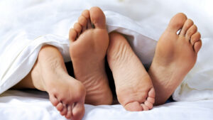 a pair of feet poking out from under a blanket implying a sexual encounter